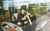 Couple having breakfast in cafe, drinking organic juices - DAPF000100