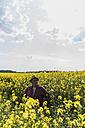 Farmer in blossoming rape field - UUF007324