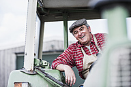 Portrait of smiling farmer on tractor - UUF007330