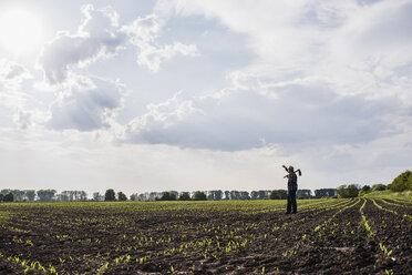 Farmer standing in a field - UUF007342