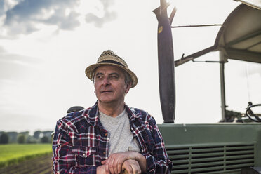 Farmer standing at tractor - UUF007348