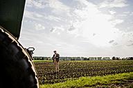 Farmer standing in a field - UUF007357