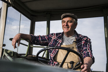 Portrait of smiling farmer on tractor - UUF007363