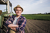 Farmer standing next to tractor at a field - UUF007366