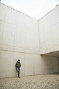 Man leaning against concrete wall looking at his smartphone - ABZF000528