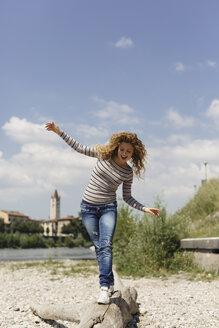 Italy, Verona, woman balancing on dead wood at riverside - GIOF001035