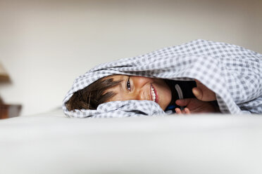 Smiling little boy lying under the blanket on his bed - VABF000509