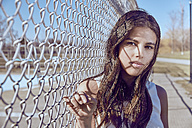 Portrait of attractive young woman at a fence - MHCF000023