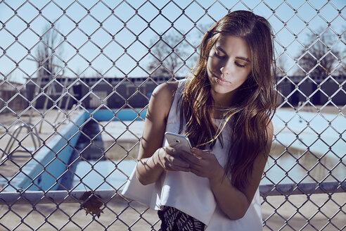 Attractive young woman at a fence looking on cell phone - MHCF000026