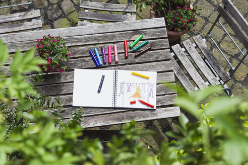 Drawing, sketch book with woman's drawing and coloring pencils on wooden garden table - GWF004704