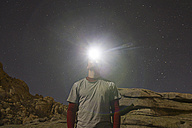 Man with headlamp under a starry sky - ABZF000533