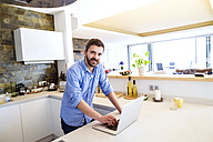 Man working in kitchen using laptop - HAPF000392