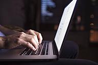 Man working at night, using laptop - HAPF000428