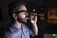 Man working at night, drinking water - HAPF000434