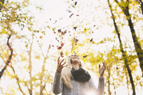 Happy teenage girl throwing up autumn leaves - SELF000090