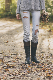 Teenage girl standing on path holding autumn leaves - SELF000093
