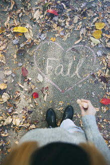 Teenage girl standing on path with autumn leaves and word fall - SELF000105