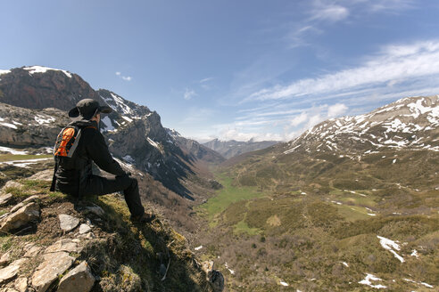 Spain, Asturias, Somiedo, man looking at the landscape sitting on mountaintop - MGOF001852