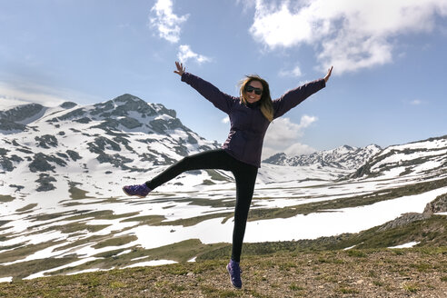 Spain, Asturias, Somiedo, playful woman jumping in mountains - MGOF001861