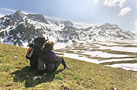 Spain, Asturias, Somiedo, couple looking at the landscape sitting in a meadow - MGOF001864