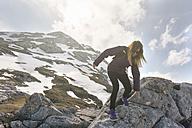 Spain, Asturias, Somiedo, woman hiking on rocks - MGOF001876