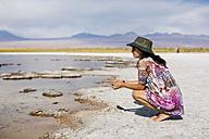 Chile, San Pedro de Atacama, woman crouching in the desert at lakeside - MAUF000604