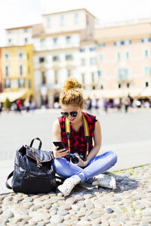 Italy, Verona, woman on town square looking at cell phone - GIOF001055