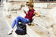 Italy, Verona, woman sitting on stairs looking at cell phone - GIOF001058