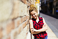 Smiling woman leaning against a brick wall - GIOF001067