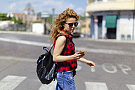 Italy, Verona, woman crossing street looking at cell phone - GIOF001085