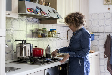 Woman at home preparing coffee on gas stove - MAUF000625
