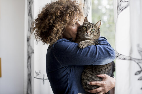 Woman cuddling with cat by the window - MAUF000640