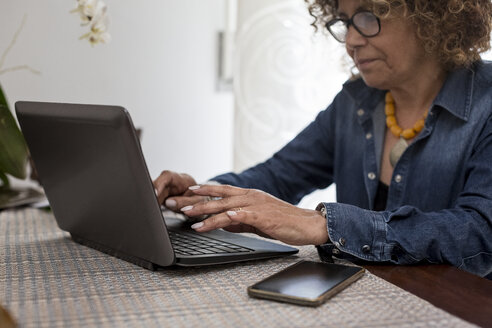 Woman using laptop at home - MAUF000643