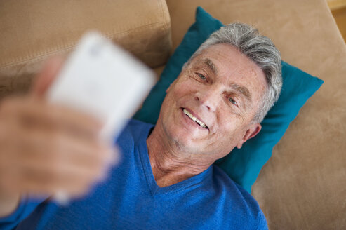 Smiling senior man lying on couch using cell phone - DIGF000492