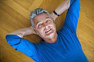 Portrait of smiling senior man lying on parquet floor - DIGF000495