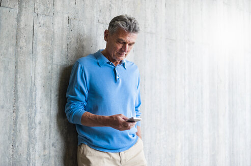 Senior man at concrete wall looking on cell phone - DIGF000558