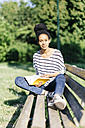 Portrait of young woman sitting on park bench with a book - GIOF001096