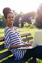 Portrait of young woman sitting on park bench using laptop - GIOF001102