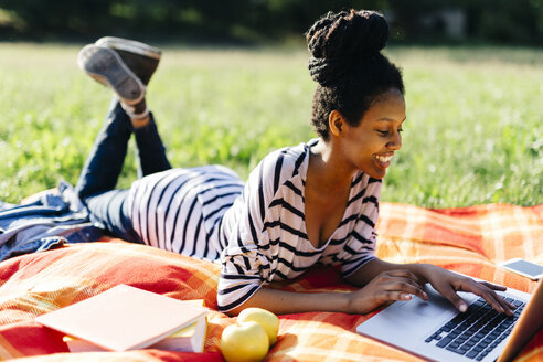 Young woman lying on blanket on a meadow using laptop - GIOF001111