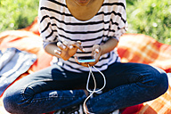 Woman sitting on blanket on a meadow using smartphone - GIOF001114
