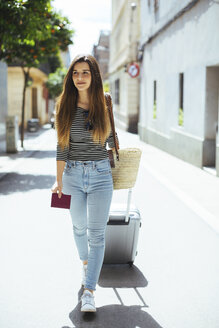 Young woman traveling with wheeled luggage - EBSF001418