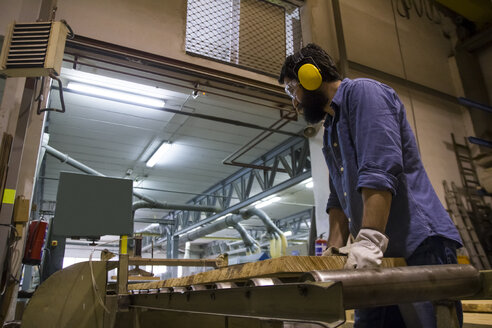 Craftsman with hearing protection, gloves and safety glasses using an industrial circular saw in a factory - ABZF000553