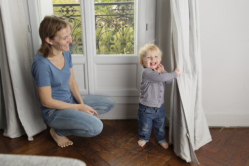 Smiling toddler playing peek-a-boo behind the curtain while his mother watching him - LITF000314