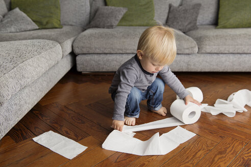 Toddler playing with a lavatory roll on the floor at home - LITF000320