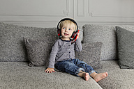 Toddler sitting on couch listening music with headphones and smartphone - LITF000323