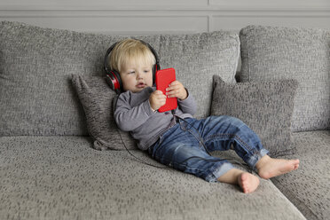 Toddler lying on couch listening music with headphones and smartphone - LITF000326