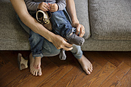 Mother's hands helping toddler putting his socks and shoes on - LITF000329