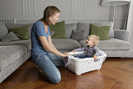 Happy toddler sitting in a laundry basket looking at his mother - LITF000332