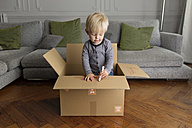 Toddler standing in a cardboard box drawing with a red marker - LITF000335