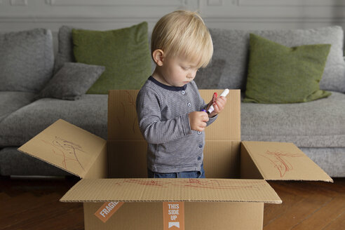 Toddler with marker standing in a cardboard box - LITF000338